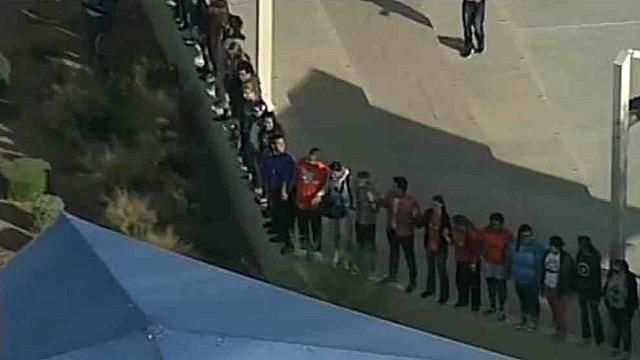 Učenici Richardsove škole  daju podršku svome ravnatelju držeći se za ruke.