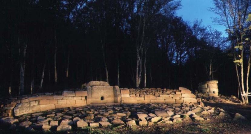 Četvrtasti dolmen s tipičnim ograđenim prostorim i neobičnim okruglim dolmenima sa strane.