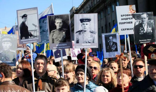 Gledatelji parade pobjede nose slke rođaka koji su ubijeni u Drugom svjestkom ratu.