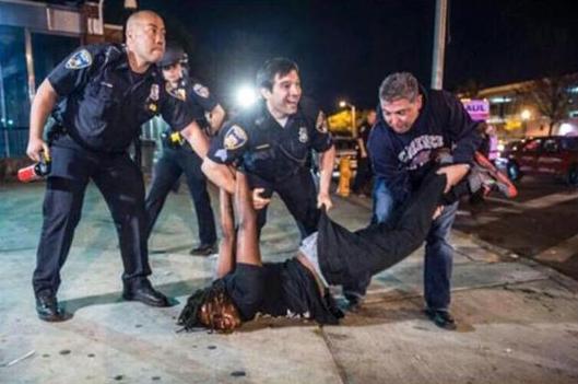 Tri policajca na jednog nenaoružanog čovjeka, obratite pažnju na osmjeh policajca u sredini.
