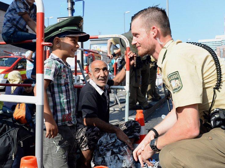Njemački policaja se igra s malenim Sirijscem na glavnom kolodvoru u Minhenu.
