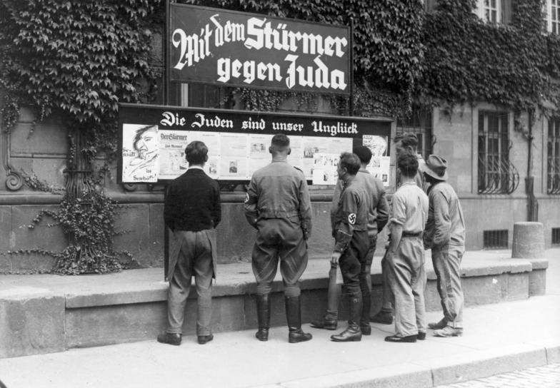 Građani čitaju propagandu s jednog od mnogobrojnih panoa koji su se pojavili nedugo nakon ustanovljenja propagandnog ministarstva.