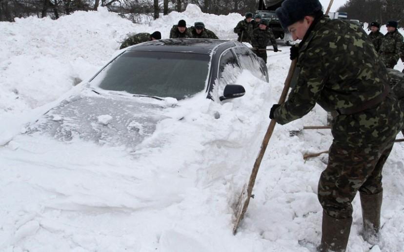 Ukrajinska vojska pomaže u otkopavanju automobila koji su ostali zameteni u mećavi pored Kijeva.