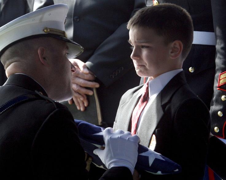 """Christian Golczynski prima zastavu tijekom vojnog pogreba za njegova oca koji je poginuo u Iraku. Na žalost mnoge obitelji nisu pokopale svoje najmilije, poginule """"heroje"""" koji su poginuli za američku demokraciju."""