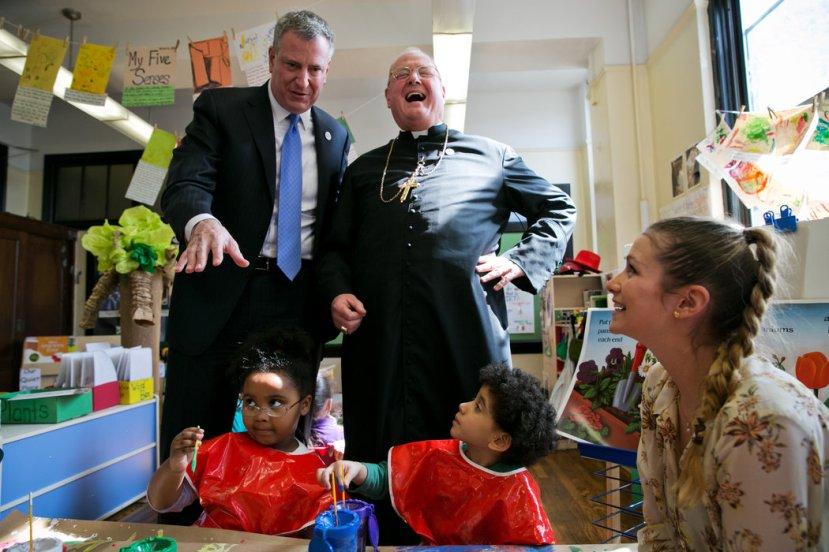 Kardinal Dolan ima razloga za smijeh nakon što je uspio onemogućiti izglašavanje zakona protiv pedofilije. Fotografija je snimljena u vrtiću Catherine Corry Early Childhood Academy u školi St. Francis of Assisi u Bronxu. S lijeve kardinalove strane vidite gradonačelnika New Yorka.